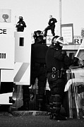 County Police Posters - PSNI riot squad officers in protective gear and snipers on crumlin road at ardoyne shops belfast 12t Poster by Joe Fox
