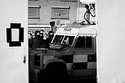 County Police Posters - PSNI surveillance land rover watches crowd on crumlin road at ardoyne shops belfast 12th July Poster by Joe Fox