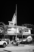 Flagpole Photos - Raising The American Flag On A Flagpole Outside The Chamber Of Commerce Building In Key Largo Florid by Joe Fox