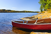 Pristine Prints - Red canoe on shore Print by Elena Elisseeva