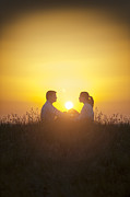 Woman In Summer Meadow Posters - Romantic Couple Sitting In Front Of A Setting Sun Poster by Lee Avison