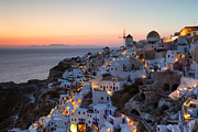 Red Buildings Prints - Romantic sunset over the village of Oia Greece Santorini Print by Matteo Colombo
