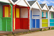 Beach Huts Posters - Row of old wooden beach huts Poster by Richard Thomas