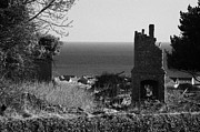 Comparison Framed Prints - ruin of an old chimney stack in a ruined ancient house overlooking modern housing and sea at Carnlough county Antrim Framed Print by Joe Fox