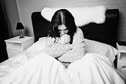 In Bed Photo Prints - Sad Early Twenties Woman Holding Cuddly Dog Soft Toy In Bed In A Bedroom Print by Joe Fox