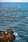 Jagged Prints - Sailboat along Rocky Coastline Print by Olivier Le Queinec