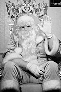 Father Christmas Prints - Santa sitting on his throne waving to camera in grotto set up Print by Joe Fox