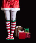Santa Claus Posters - Santas Elf legs next to a pile of Christmas gifts over black Poster by Edward Fielding