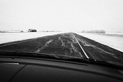 Winter Roads Prints - snow blowing over road while winter driving along Saskatchewan highway 11 from Saskatoon to Regina C Print by Joe Fox