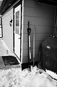 Shovels Prints - snow clearing shovels and scoops outside doorway of building Forget Saskatchewan Canada Print by Joe Fox