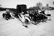 Snowmobile Framed Prints - snowmobiles parked in Kamsack Saskatchewan Canada Framed Print by Joe Fox