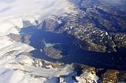 Sami Sarkis - Snowy rocky coastline and floating icebergs on ocean