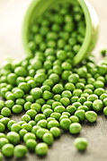 Vegetarian Posters - Spilled bowl of green peas Poster by Elena Elisseeva