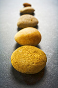 Stepping Prints - Straight Line of Brown Pebbles on Dark Background Print by Colin and Linda McKie