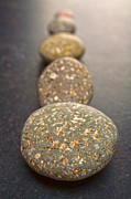 Stepping Prints - Straight Line of Speckled Grey Pebbles on Dark Background Print by Colin and Linda McKie