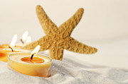 Sandra Cunningham - Tea light candles in sand with star fish