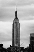 Manhaten Posters - Top Of The Empire State Building Above Skyline And Grey Cloudy Sky New York City Poster by Joe Fox