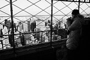 Manhatten Framed Prints - Tourist In Heavy Coat And Camera Looks At The View From Observation Deck 86th Floor Empire State  Framed Print by Joe Fox