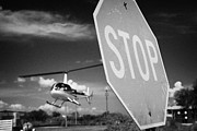 Stop Sign Framed Prints - Tourist Light Helicopter Landing Behind Stop Sign Kissimmee Florida Usa Framed Print by Joe Fox