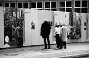 West Berlin Framed Prints - tourists read the history of the berlin wall at checkpoint charlie Berlin Germany Framed Print by Joe Fox