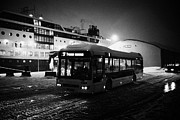 Cold Night Posters - Tromso public bus passing hurtigruten ferry quay at night during winter troms Norway europe Poster by Joe Fox