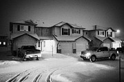 Snow Falling Prints - truck driving through street with snow falling in residential neighborhood in Saskatoon Saskatchewan Print by Joe Fox