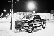 Snowstorm Art - truck parked on the main street at night in snowstorm Biggar Saskatchewan Canada by Joe Fox