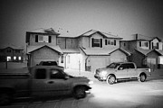 Snow Falling Prints - trucks driving through street with snow falling in residential neighborhood in Saskatoon Saskatchewa Print by Joe Fox