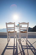 Emptyness Posters - Two empty chairs overlooking blue mediterranean sea in Santorini Poster by Matteo Colombo