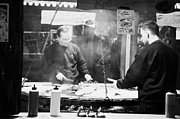 Berlin Germany Prints - Two men on a fast food meat selling stall cook rostbratwurst and steak on a huge open grill spandau christmas market Berlin Germany Print by Joe Fox