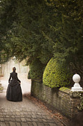 Ally Photos - Victorian Woman Walking On A Cobbled Path With Wall And Topiary by Lee Avison