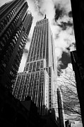 Manhaten Framed Prints - View of the empire state building and surrounding buildings and  cloudy sky from West 33rd Street ny Framed Print by Joe Fox