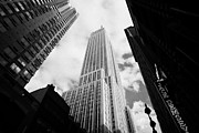 Manhatten Framed Prints - View of the empire state building and surrounding buildings and cloudy sky West 33rd Street new york Framed Print by Joe Fox