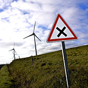 Power Photos - Wind turbines on the edge of a field with a road sign in foreground. by Bernard Jaubert