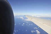 Sami Sarkis - Wing and jet engine of airplane flying over ocean