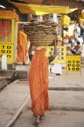 Basket Head Framed Prints - Woman Carrying Cow Dung In Basket On Framed Print by Paul Miles