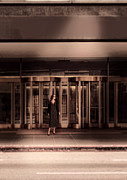 Glass Reflections Framed Prints - Woman Standing by Revolving Doors Framed Print by Jill Battaglia
