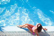 Suntanned Framed Prints - Woman sunbathing by the swimming pool Framed Print by Matteo Colombo