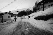 Ice-covered Prints - woman walking down steep ice covered street in Honningsvag finnmark norway europe Print by Joe Fox