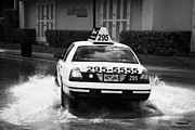 Flooding Posters - Yellow Taxi Cab Driving Through Streets Flooded By Heavy Rainfall Key West Florida Usa Poster by Joe Fox