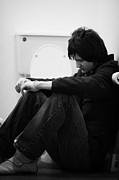 Young Man Photo Prints - Young Dark Haired Teenage Man Sitting On The Floor Of The Bathroom With Back Against The Wall In The Print by Joe Fox