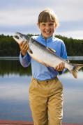 Coho Salmon Posters - Young Girl Holding And Posing With A Poster by Michael DeYoung