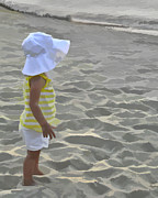 Sun Hat Prints - Young girl on beach with hat. Print by Jack Nevitt