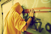 Hooded Figure Prints - Young man on graffiti grunge wall Print by Michal Bednarek