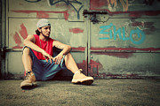 Adolescence Prints - Young man sitting Grunge graffiti wall Print by Michal Bednarek