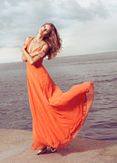 Fluttering Posters - Young woman in orange dress flying in the wind at sea shore Poster by Oleksiy Maksymenko