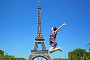 Enjoying Prints - Young woman jumping against Eiffel Tower Print by Michal Bednarek