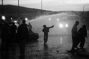 Unrest Framed Prints - Youths Rioting Throwing Stones With Burned Out Car Being Hit By Water Canon On Crumlin Road At Ardoy Framed Print by Joe Fox