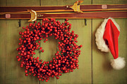 December Prints -  Red wreath with Santa hat hanging on rustic wall Print by Sandra Cunningham