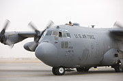 Taxiway Prints - A C-130 Hercules Aircraft Taxis Print by Terry Moore
